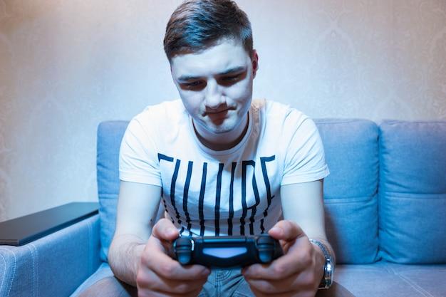 텔레비전 앞 소파에 앉아 콘솔을 검사하는 청년, 집에 있는 세트에서 푸른 빛으로 정면 전망