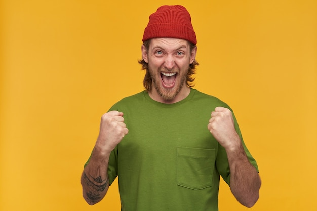 Молодой человек, возбужденный парень со светлыми волосами, бородой и усами. в зеленой футболке и красной шапке. имеет татуировку. сжать кулаки. изолированные над желтой стеной