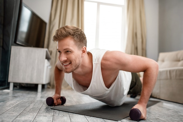 Young man exercises at home