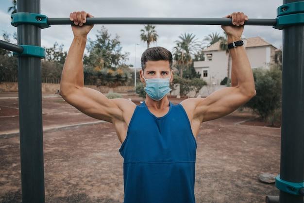 Молодой человек упражнения с маской для лица на открытом воздухе