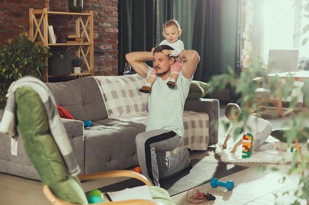 Giovane uomo esercizio fitness, aerobica, yoga a casa, stile di vita sportivo.