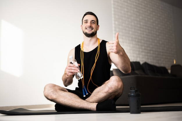 Young man exercising at home. guy sits alone on black yoga map, holds water bottle and thumbs up. yellow jumping rope around neck. athletist rest and relax. small break.