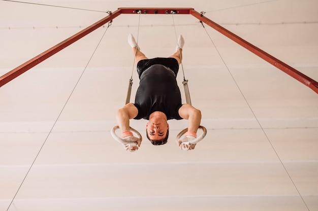 Молодой человек тренируется на кольцах гимнастики