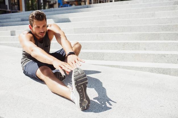 外で運動する若い男。階段の横に座って腕と脚を伸ばしているスポーツマンのビュー。ヨガの練習をしています。夏の間、路上でのトレーニングとトレーニング。