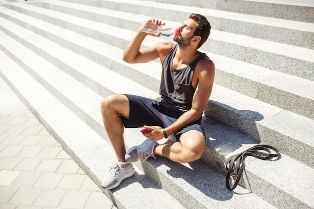 外で運動する若い男。アスリートは外の階段に座って、どきどきします。水を飲んで楽しんでください。手に電話を持っています。トレーニングや運動後の疲れたスポーツマン。