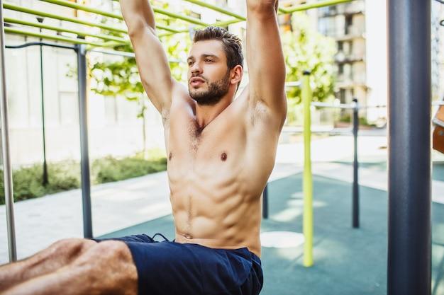 外で運動する若い男。鉄棒にぶら下がっている強力で強力な筋肉質の男のクローズアップとカットビュー
