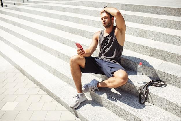 外で運動する若い男。集中力のあるアスリートは、トレーニング後に階段に座ってリラックスします。携帯電話を手に持って見ています。