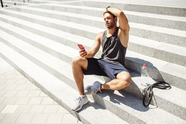 Young man exercising outside. concentrated athlete sit on steps after training and relax. holding phone in hand and looking on it.