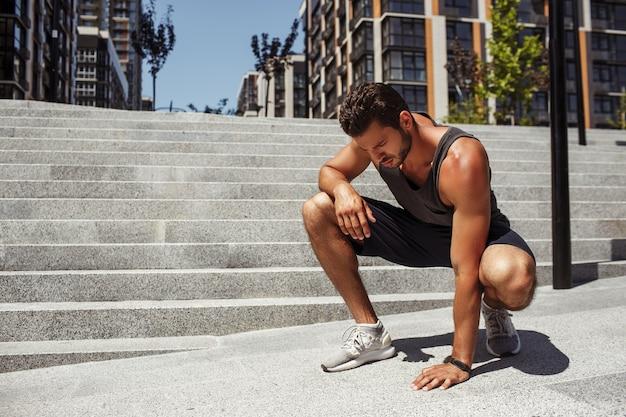 外で運動する若い男。アスファルトに触れて見下ろす集中真面目な男。運動、ランニング、ジョギングをした後は休憩してください。階段の近くでしゃがんだ姿勢で一人で座ります。