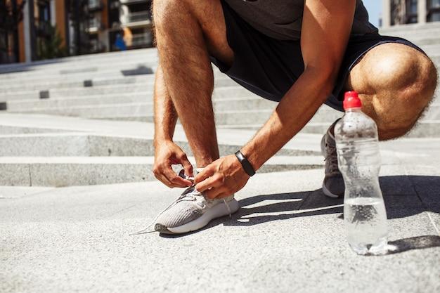 外で運動する若い男。靴やスニーカーの靴ひもを結ぶ男性の低いビューをカットします。アスファルト以外にほとんど空の水筒。