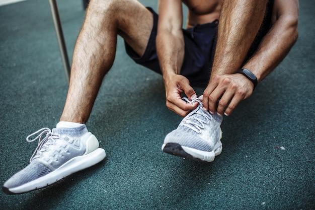 外で運動する若い男。 froundとネクタイの靴ひもに座っているスポーツマンのカットビュー。運動の準備。スリムでしっかりとした筋肉質の脚とふくらはぎ。