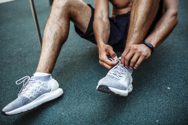 Young man exercising outside. cut view of sportsman sitting on fround and tie shoe laces. preparing for exercising. slim well built muscled legs and calfs.