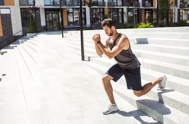 外で運動する若い男。手をつないで、階段を下りるときに片足でスクワット運動をしている男。日照期間中の屋外での都市トレーニング。