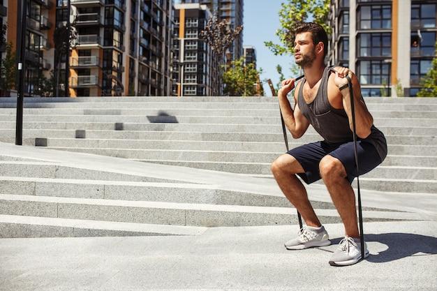 外で運動する若い男。肩に輪ゴムを持ってスクワット運動をしている男。ハード集中トレーニングまたはトレーニング。一人で外で運動する。