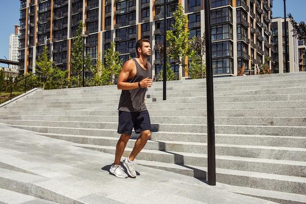 外で運動する若い男。男のジョギングやステップ以外のスローランニング。外でトレーニングやトレーニングをする。夏の間は新鮮な空気で運動します。健康的な生活様式。