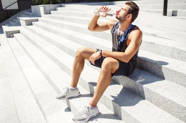 外で運動する若い男。男はハードワークアウトの後に階段と飲料水に一人で座っています。首の周りの青い縄跳び。日差しの下で座っています。アスリートは休んでリラックスしてください。小さな分裂。