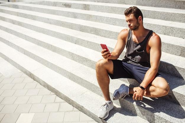 밖에 서 운동하는 젊은 남자. 남자는 열심히 운동 후 계단에 앉아 휴식을 취합니다. 스마트 폰을 손에 들고 바라보세요. 섹시 잘 생긴 선수 포즈. 현대 기술 및 장치.