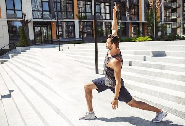 外で運動する若い男。セミスクワットの姿勢で立っている男性、または手を上下に同時に保持しているヨガのポーズ。男は体と体型の世話をします。外で一人でトレーニング。