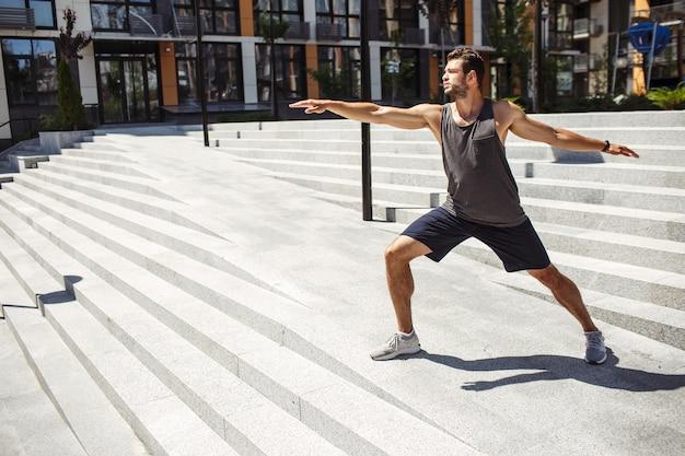 外で運動する若い男。一人でヨガのポジションに立って、手を前後に伸ばしている男。体の世話をします。アーバントレーニング。素晴らしい幸福。