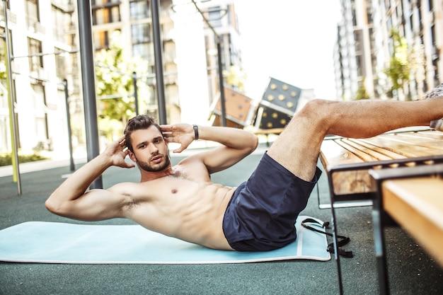 外で運動する若い男。ハンサムなセクシーな上半身裸のスポーツマンは、最高のコアマッスルのためにエクササイズで腹筋をトレーニングし、それらを強く保ちます。遊び場だけでトレーニングをします。