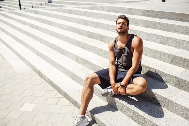 外で運動する若い男。白い階段に座ってカメラでポーズをとるホットな格好良いセクシーなハンサムなアスリート
