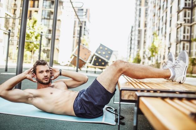 外で運動する若い男。腹筋運動の姿勢を保つ男の写真。