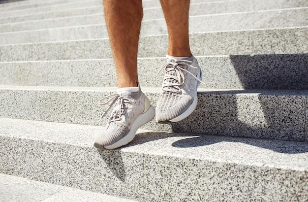 外で運動する若い男。日光や日光の当たる外の階段を歩いているスニーカーの男の足の写真。路上で運動する小さなトレーニング。足から日陰。