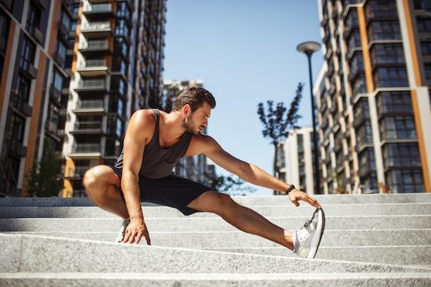 外で運動する若い男。強い男が足を伸ばして手で持っている写真。ヨガのポジションで一人で立っています。運動前にウォーミングアップするか、ストレッチでトレーニングを終了します。