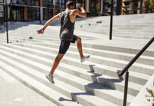 밖에 서 운동하는 젊은 남자. 거리에서 여러 단계를 뛰어 넘는 강한 빠른 남자의 측면 후면보기. 강력한 운동가 훈련 또는 운동. 몸의 힘을 키우고 있습니다.