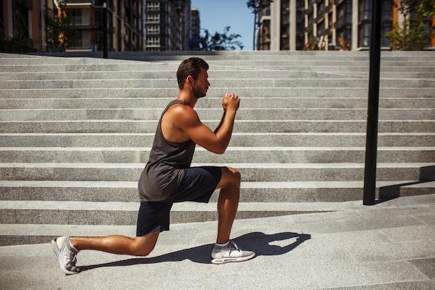 外で運動する若い男。片足スクワットの位置に座って、自分の前で手をつないでいる男の運動選手の側面図。トレーニングまたはトレーニング。