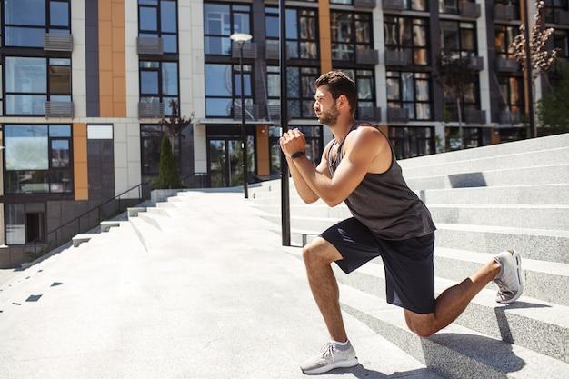 外で運動する若い男。片足で下り坂のエクササイズスクワットを下りるスポーティなアスリートの側面図。都市の建物で外でトレーニング。一緒に手を取り、運動に集中します。