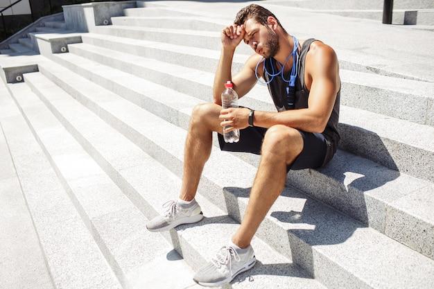 外で運動する若い男。運動後は、階段に座って休憩します。水のボトルを保持しています。首に縄跳びをする。運動後はリラックスしてください。