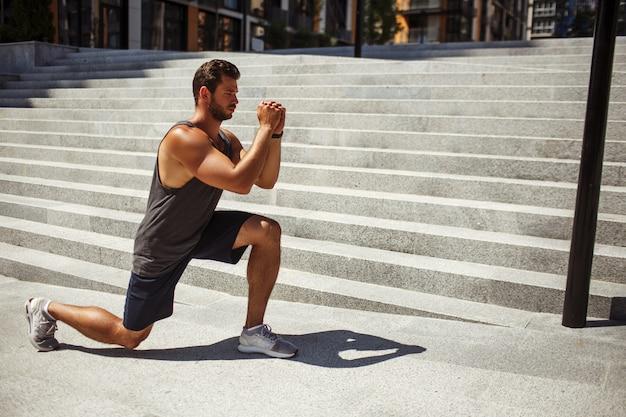 外で運動する若い男。強くて力強い男が片方の膝の上に立ち、自分の前で手をつないでいます。片足スクワット運動をする。彼の体と筋肉を訓練します。