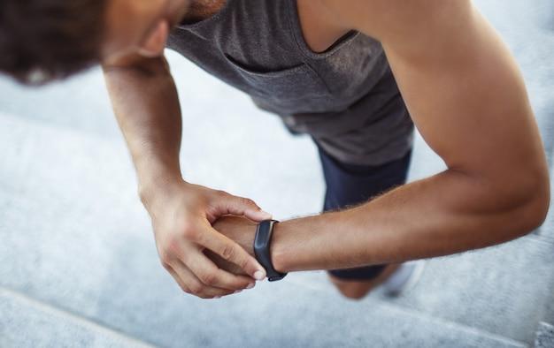 外で運動する若い男。彼の手でフィットネストラッカーで彼の結果をチェックする強力な強力な男のアップビュー。時間追跡。階段を歩く。
