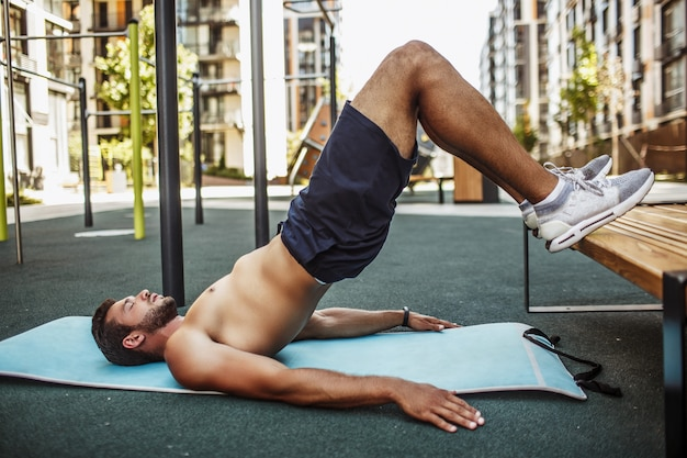 外で運動する若い男。しっかりと構築された筋肉質の男は、脚を上にして逆板の位置に立っています。地面に手をつないでトレーニングします。遊び場で一人で。
