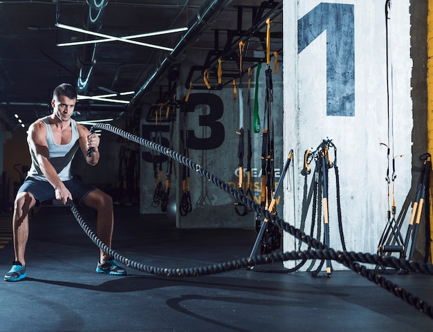 Young man exercising with battle ropes