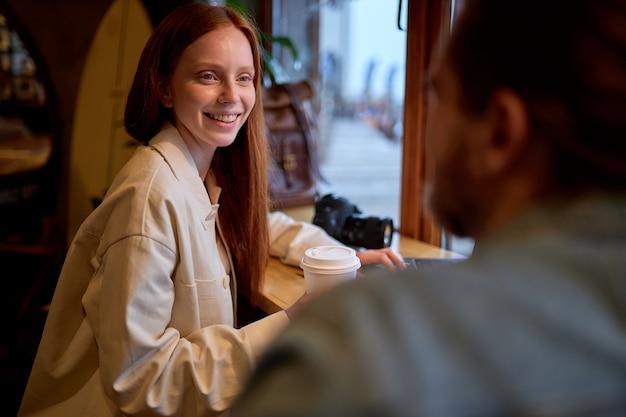 赤毛の女性パートナーに新しい相互ビジネスのアイデアを説明する若い男