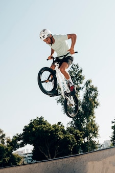 Young man extreme jumping with bicycle low angle view
