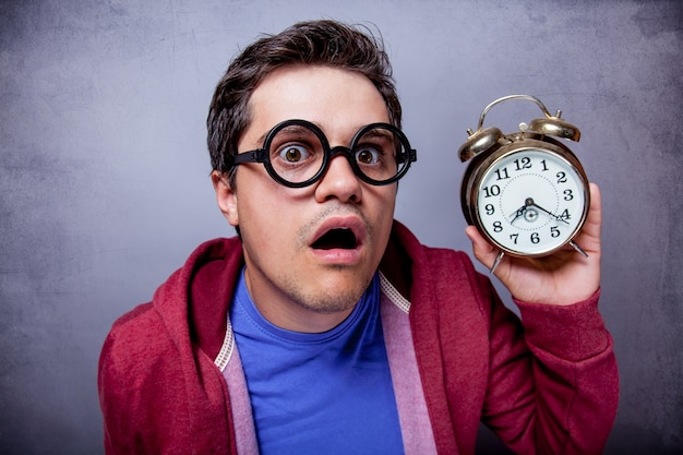 Young man in eyeglasses with metal alarm clock on grey