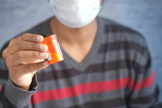 Young man in face mask holding medical pills container