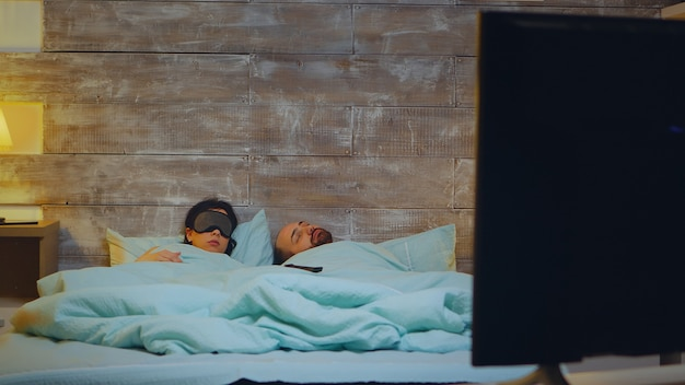 パジャマ姿でテレビを見ながら眠りに落ちる若い男。睡眠マスクを持つガールフレンド。