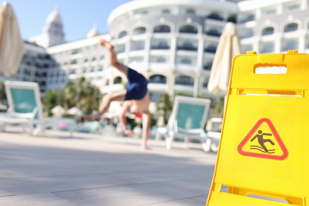 Young man falling on slippery tiles in street near yellow warning sign closeup