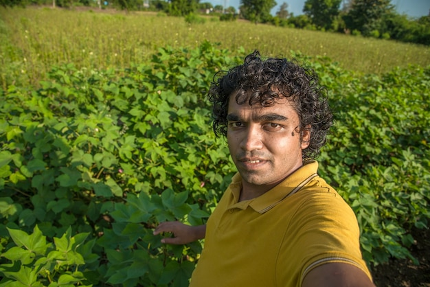 Young man farmer in a cotton farm taking selfie using a smartphone or camera.