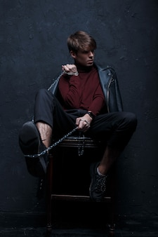 A young man in a fashionable jacket in a stylish burgundy golf in black pants and stylish sneakers with a metal chain, posing sitting on a chair in a room near the black wall. attractive stylish guy