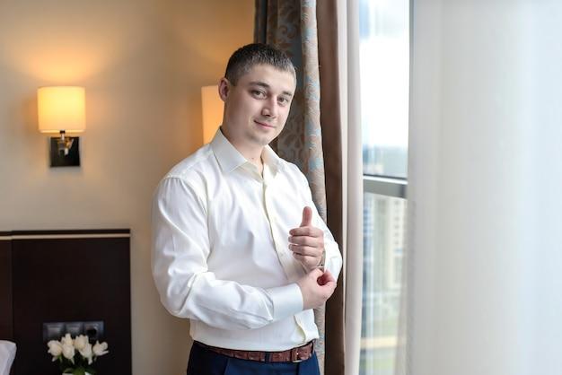 袖のボタンを締める若い男