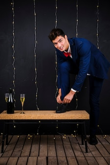 Young man fastening shoe laces near glass and bottle of champagne