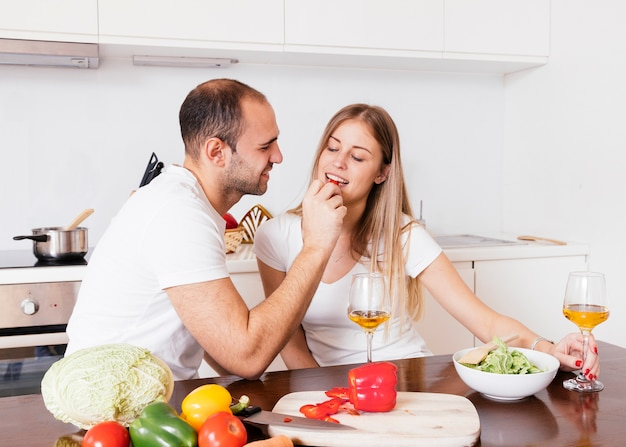 Young man feeding bellpepper to her wife with wineglasses on wooden table