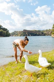 Молодой человек кормит гусей на берегу реки