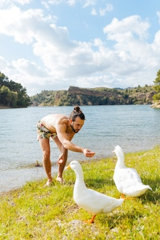 Young man feeding gooses on riverbank