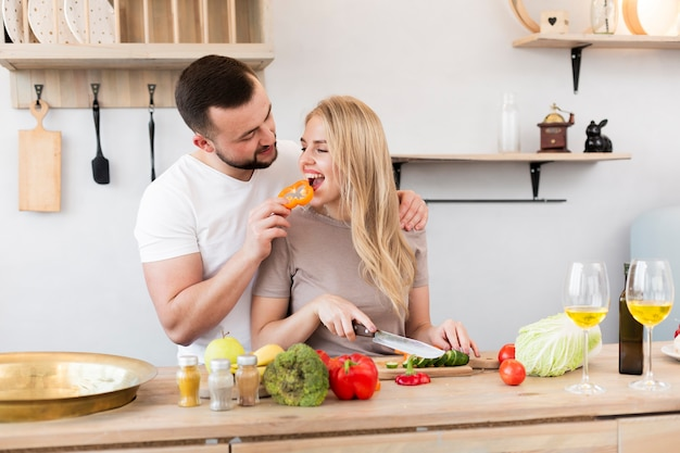 Young man feeding his woman with bell pepper